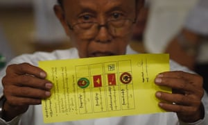 A poll official displays a ballot marked for Aung San Suu Kyi's NLD party.