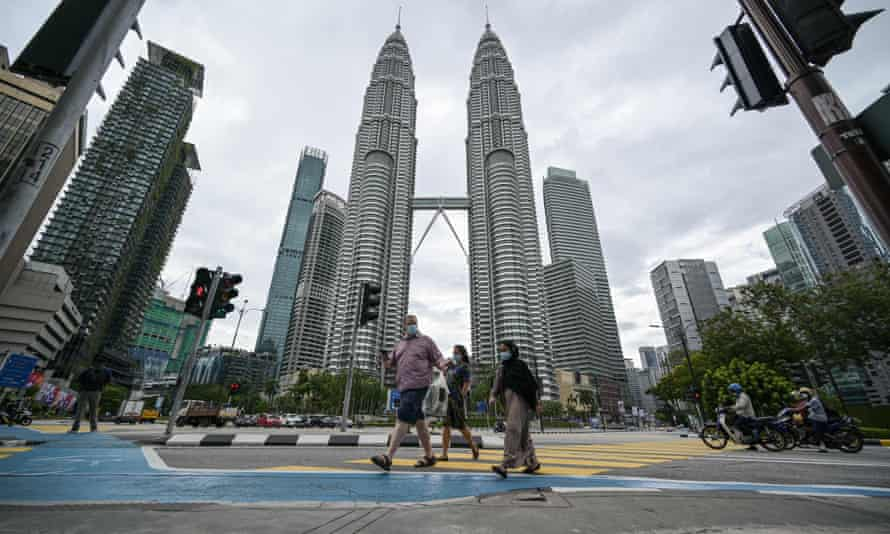 people walk in front of malaysia's petronas towers