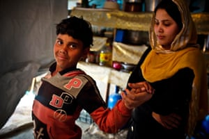 Ali, who is nine and disabled, is helped by his sister Fatima, 18, in their new home in Zahlé