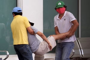 Men carry a sick man into a hospital in Guayaquil, Ecuador on Wednesday