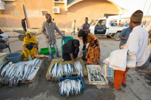 Traders lay fish out for sale under the watchful eye of a policeman in Nouakchott.