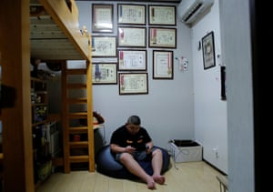 Kumagaiplay s a video game in his bedroom. On the walls are prizes and medals won in sumo competitions