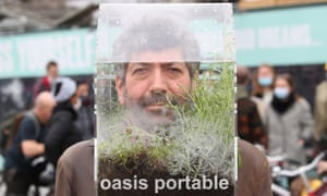 """Belgian artist Alain Verschueren wears his """"Portable Oasis"""" while performing in BrusselsBelgian artist Alain Verschueren wears his """"Portable Oasis"""" while performing in a street, saying he wanted to be in his bubble in the middle of the city."""