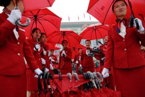 Ushers manage umbrellas used by delegates arriving for the opening session