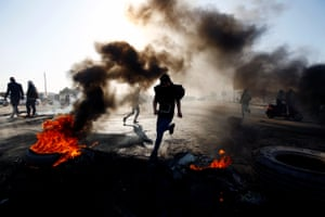 An Iraqi demonstrator runs between burning tyres blocking a road during ongoing anti-government protests in Najaf.