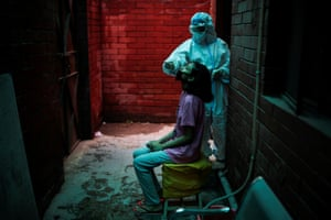 New Delhi, India. A health worker in personal protective equipment tests a member of the public for coronavirus
