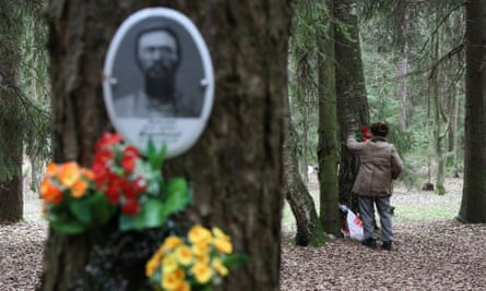 A man places a candle at the photo of a relative who was killed and buried in 1937.