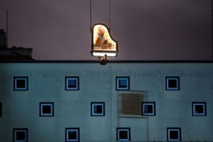 The Swiss artist Alain Roche plays piano while hanging from a crane in Munich, Germany