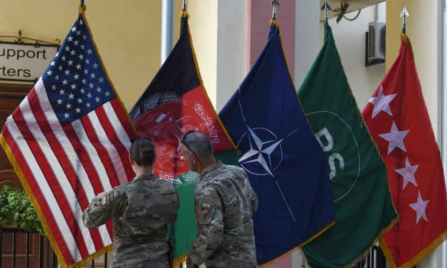 US military personnel adjust US and Afghan national flags in Kabul.
