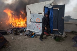 A man in a the Calais camp taking his belongings
