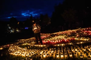 Zella-Mehlis, Germany. Gertrud Schop lights candles arranged in the shape of a cross, dedicated to each of the country's covid-19 victims