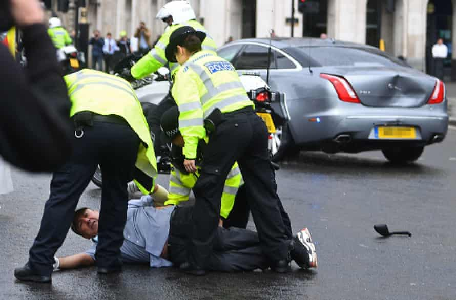 Police detain a man after the incident outside parliament.