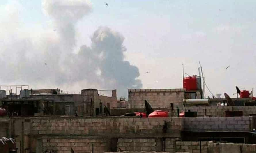 Smoke billows from bomb-stricken buildings in Homs, Syria.