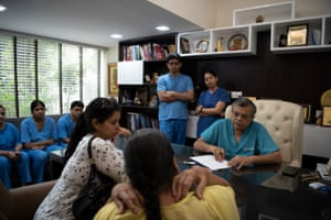 Dr GP Dureja, surrounded by medical trainees, talks to a patient at the Delhi Pain Management Centre.