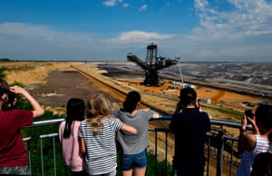 Visitors take a picture of a bucket-wheel excavator at a mine in Jackerath, Germany