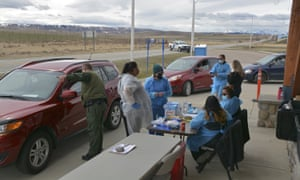 A US Border Patrol agent directs a driver after the passenger received a Covid-19 vaccine from nurses of the Blackfeet tribe at the Piegan-Carway border crossing near Babb, Montana.