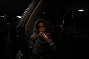 Mia Toleafoa drinks a slurpee in the back of her parents' van