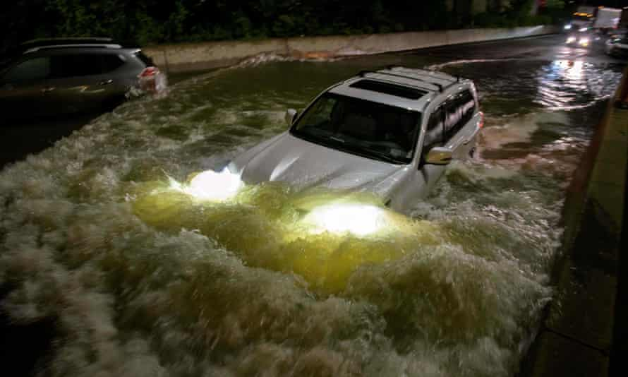 A motorist drives a car through a flooded expressway in Brooklyn, New York, early on Thursday, as flash flooding and record-breaking rainfall brought by the remnants of Storm Ida swept through the area.