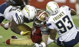Colin Kaepernick is sacked by Dwight Freeney, Ricardo Mathews of San Diego, in a San Francisco home game in December 2014.