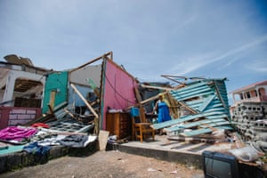 A woman stands amid the ruins of her home in Roseau. Almost 100% of buildings on the island were damaged or destroyed by the hurricane