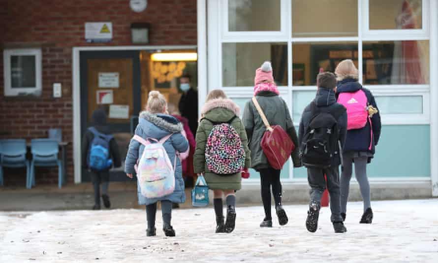 Primary school children enter a school