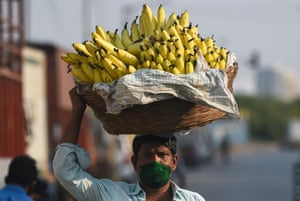 A man carrying a basket filled with bananas in Mumbai, India