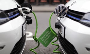 A pair of Zipcar club car-sharing Volkswagen Golf GTE plug-in petrol-electric hybrid cars being recharged on a street in London