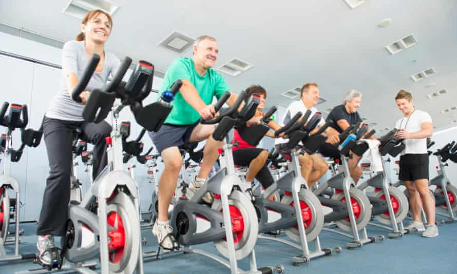 Low angle view of people riding spin bicycles in gym.