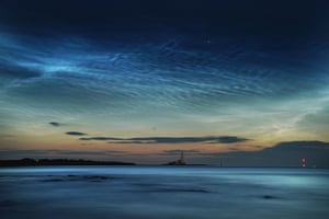 Whitley Bay, England Rare noctilucent clouds shine brightly across Whitley Bay beach over St Mary's Lighthouse