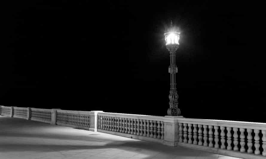 A single light shines in the darkness on the promenade in Cádiz, Spain