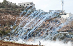 Teargas canisters are fired by Israeli troops towards Palestinians during a protest against Israeli land seizures for Jewish settlements near Ramallah in the occupied West Bank.