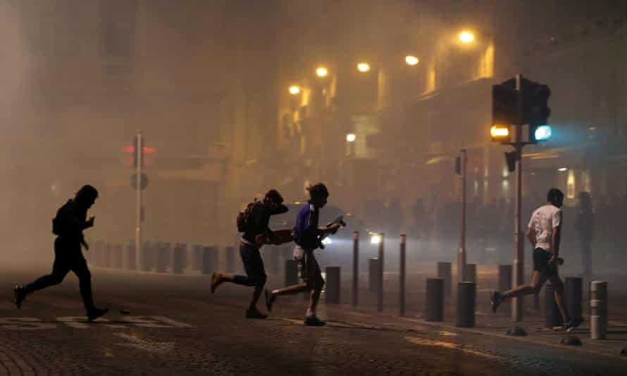 People in Marseille's old port area run away after police use tear gas to disperse rival groups following England's match against Russia.