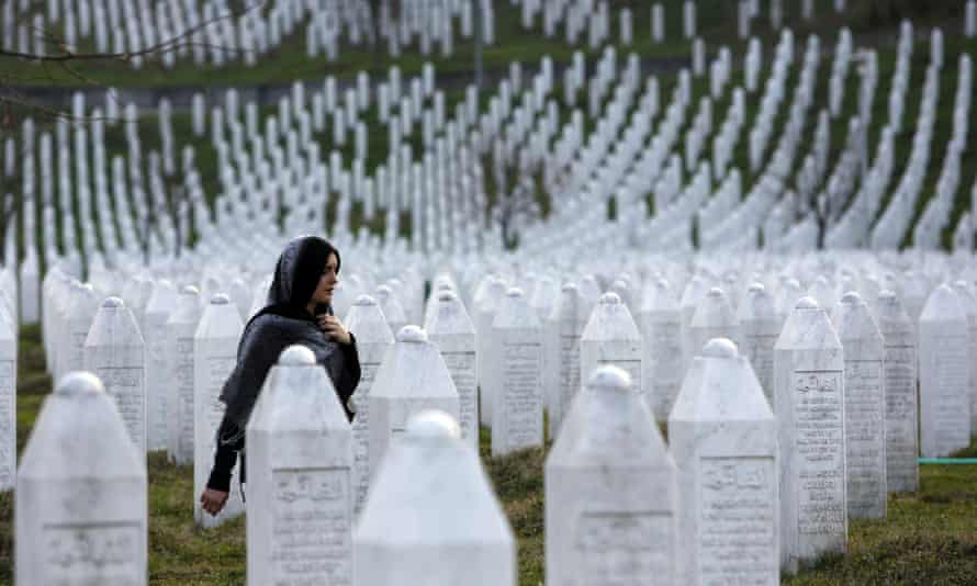 A Bosnian woman walks among gravestones at the Potocari memorial centre near Srebrenica, in Bosnia and Herzegovina