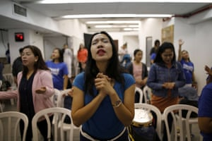 Merry Christ Palacios, a caregiver from the Philippines, prays during a church service held at the station