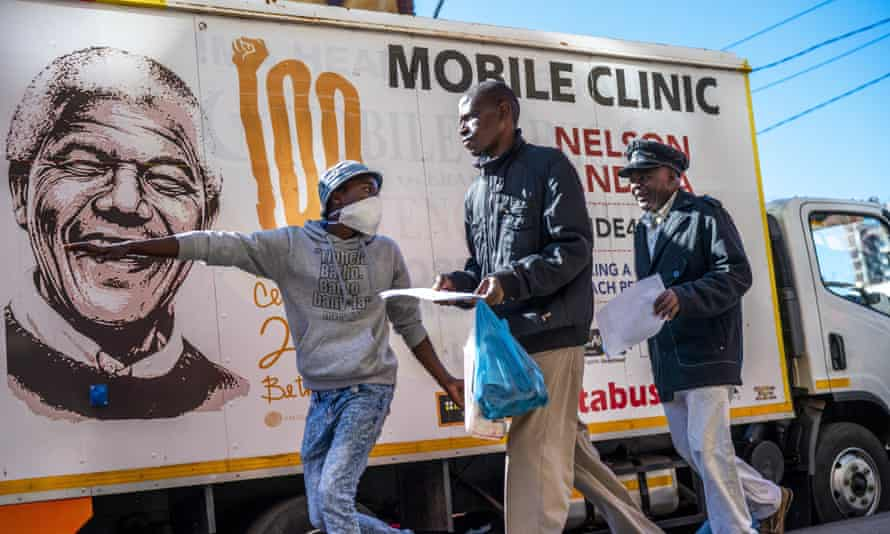 A volunteer directs two men towards a medical tent where they will be tested for Covid-19 as well as HIV and TB, in downtown Johannesburg.