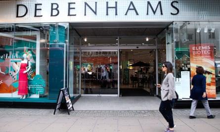 Shoppers pass a Debenhams store in London
