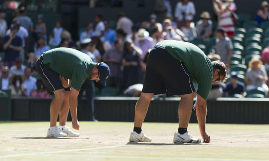 Wimbledon grounds staff repair court surfaces between matches on day six.