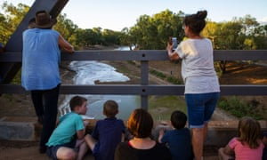 people stand on a bridge watching water flow into a dry river bed