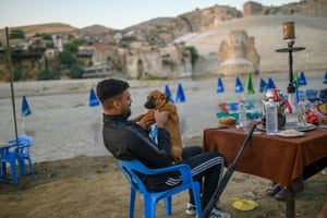Devran Tunc, 28, owner of a coffee shop next to the Tigris River in the city centre, plays with his dog in Hasankeyf on August 17, 2019