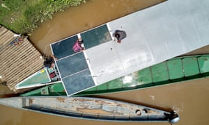 A team of indigenous technicians installs solar panels on the roof of a new canoe
