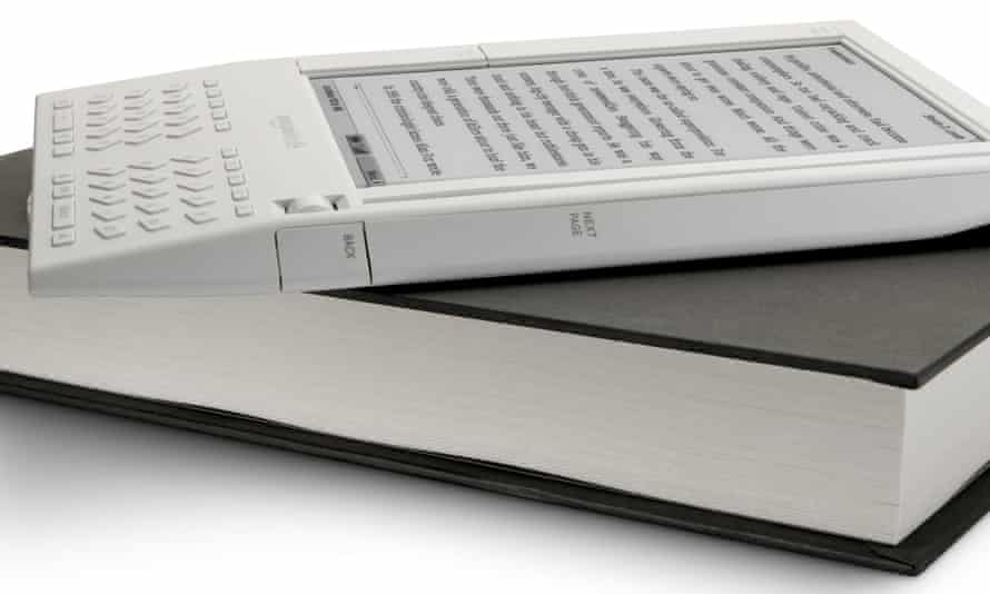 E-reading on top … one of the first Kindles rests on a traditional book.