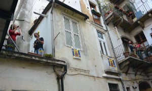 Maksim Cristan and Daria Spada perform from a balcony in the centre of Turin
