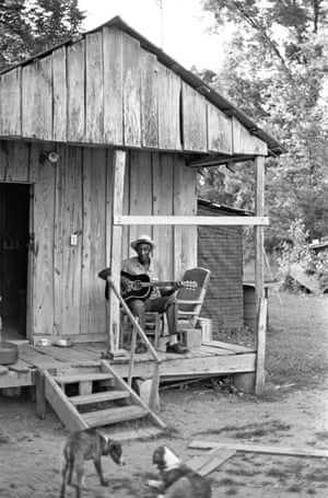 Scott Dunbar plays guitar on his front porch.