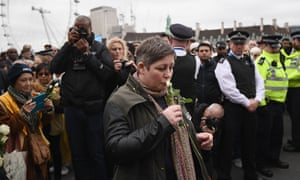 A woman kisses a white rose on Westminster Bridge during the vigil