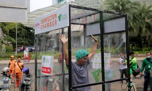 A woman is sprayed in a makeshift disinfection chamber in Jakarta where tehere have been hundreds of cases of Covid-19.