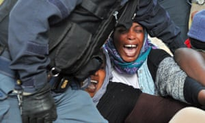 Italian police use force to remove people, mostly from Sudan and Eritrea, who have been camped out for days near the border crossing with France.