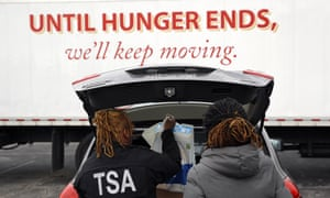 TSA officers Princess Yang, left, and Erica Gibbs charge food in a car after visiting the Baltimore food pantry.