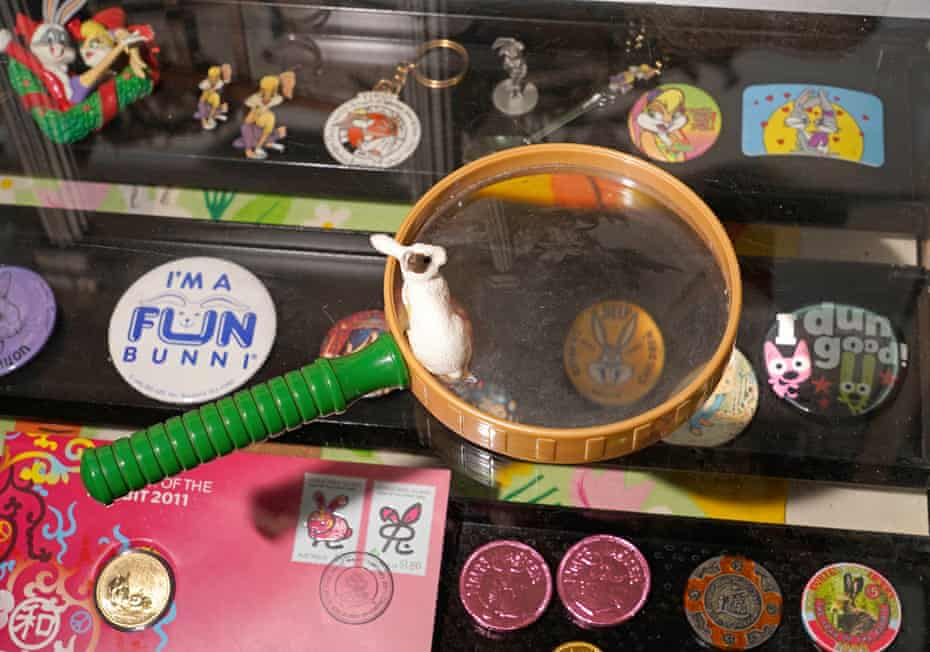 A display case containing the museum's smallest items, including pins, coins, and key rings, with a magnifying glass on top.