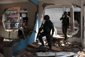 Army soldiers check the damage at a destroyed police post during a security operation at Barbante favela in Rio de Janeiro.