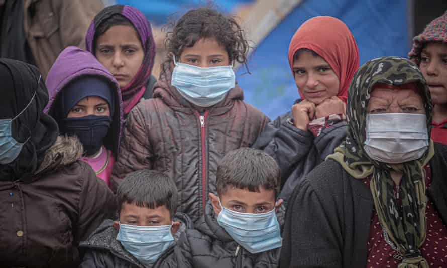 Children and an elderly woman wear masks as a preventive measure against the coronavirus in Idlib.